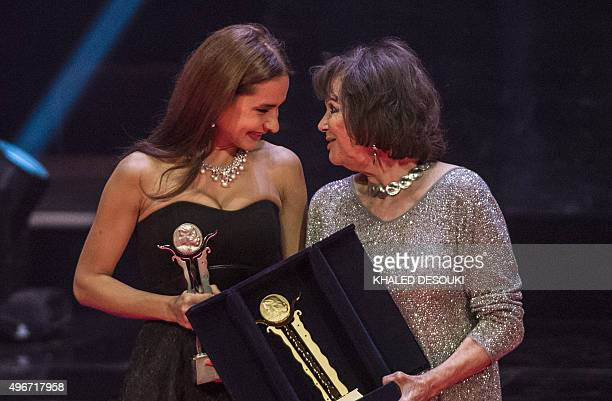 Italian actress Claudia Cardinale and Egyptian actress Nelly Karim talk on stage after receiving honorary awards during the opening ceremony of the...