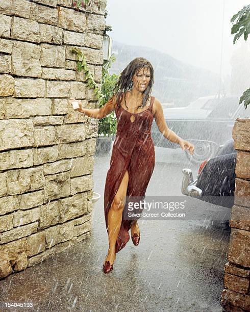 Italian actress Claudia Cardinale as Laura Califatti running through the rain in 'Don't Make Waves' directed by Alexander Mackendrick 1967