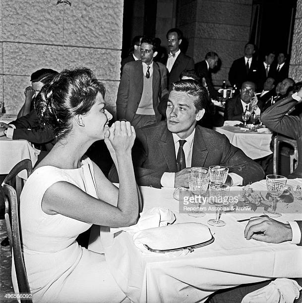 Italian actress Claudia Cardinale dining at the restaurant 'Vecchia America di Corsetti' for the Cinema Gala with French actor Alain Delon Rome 1961