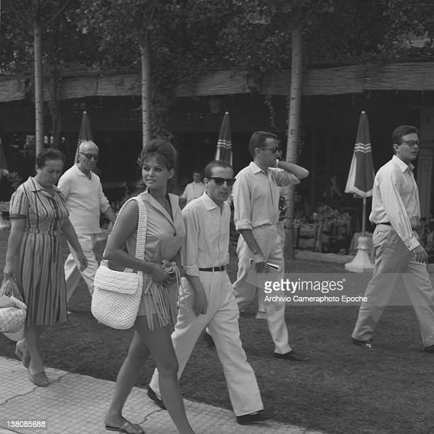 Italian actress Claudia Cardinale during a walk in Lido surrounded by fans and her staff Lido 1960