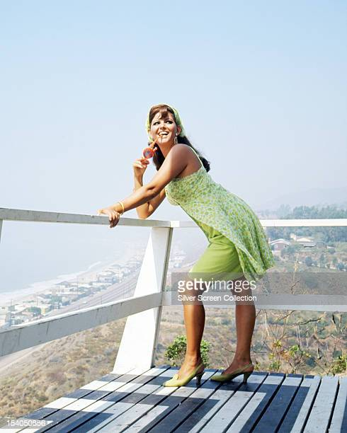 Italian actress Claudia Cardinale leaning on a balcony overlooking a beach circa 1967