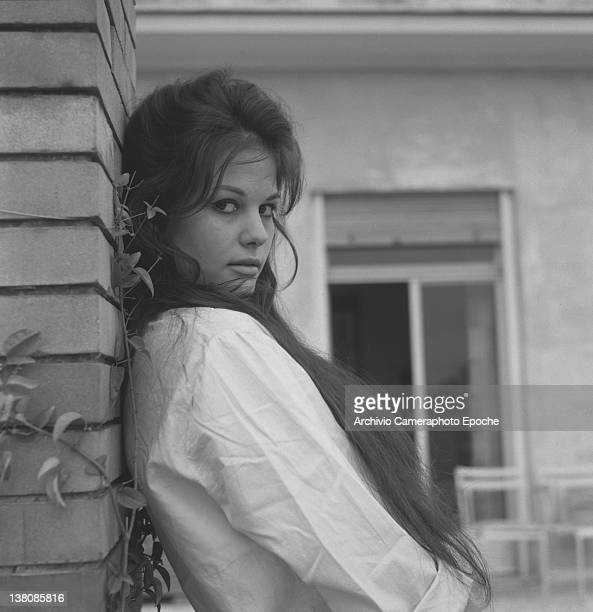 Italian actress Claudia Cardinale leaning on a wall wearing a white shirt Rome 1959