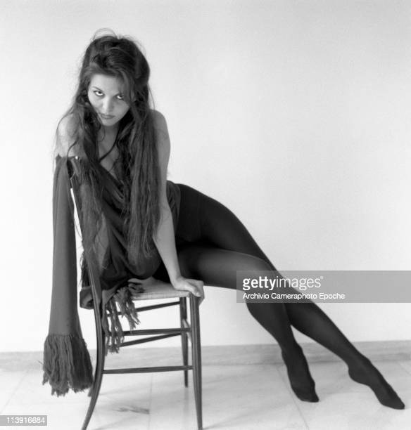 Italian actress Claudia Cardinale, long-haired, sitting on the side, on a chair, wearing black tights and a scarf, Rome 1959