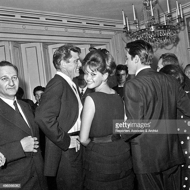 Italian actress Claudia Cardinale looking at the photographer and smiling while talking to American actor Burt Lancaster and French actor Alain Delon...