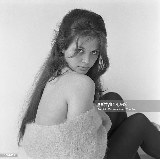 Italian actress Claudia Cardinale, looking behind her right shoulder, wearing a woolen scarf and black tights, Rome 1959.