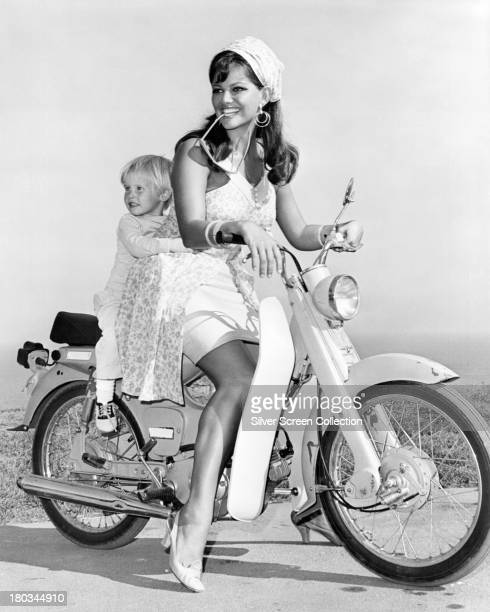 Italian actress Claudia Cardinale, on a motorcycle with a child during the filming of 'Don't Make Waves', directed by Alexander Mackendrick,...