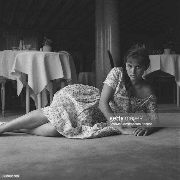 Italian actress Claudia Cardinale portrayed while lying on a restaurant's floor wearing a plait and a floral dress Venice 1958