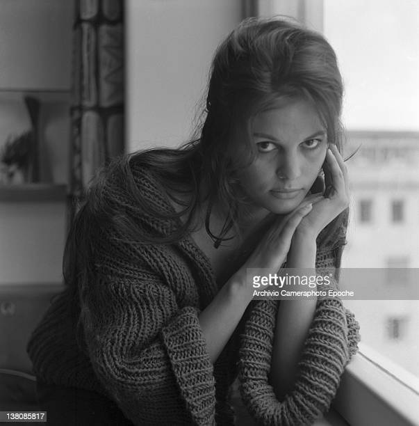 Italian actress Claudia Cardinale portrayed while wearing a woolen jumper, sitting close to a window, Rome, 1959.