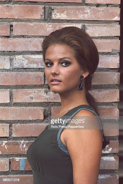 Italian actress Claudia Cardinale posed standing in front of a brick wall circa 1966