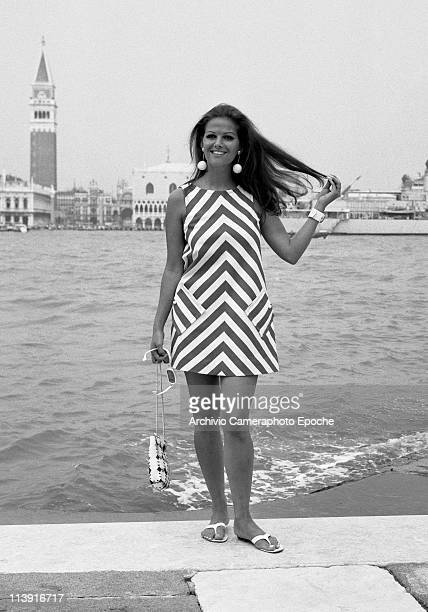 Italian actress Claudia Cardinale posing on the island of Giudecca, in front of St. Mark Square, wearing an optical dress and white round dangling...
