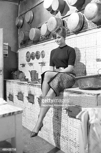 Italian actress Claudia Cardinale posing sitting in the kitchen of the set of the film Il bell'Antonio 1959