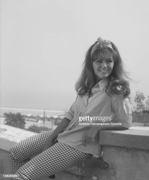 Italian actress Claudia Cardinale sitting on a balustrade, Lido, Venice,1960.