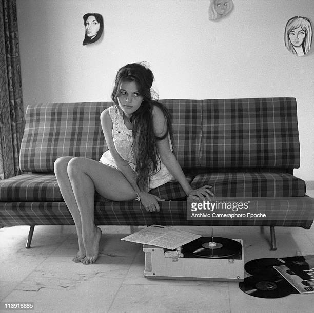 Italian actress Claudia Cardinale sitting on a plaid sofa listening to Ella Fitzgerald vynils, with drawn faces hanging on the back wall, Rome 1959.