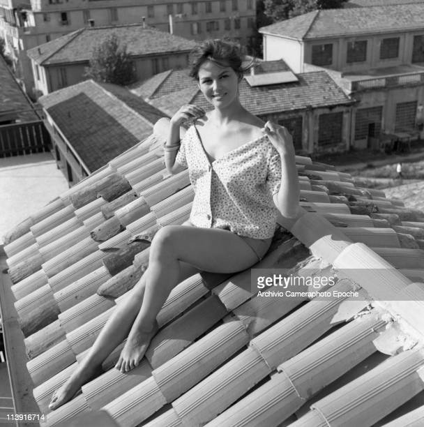 Italian actress Claudia Cardinale sitting on the roof top, wearing hotpants, a shirt and some bangles, baring her shoulders, Rome, 1958.