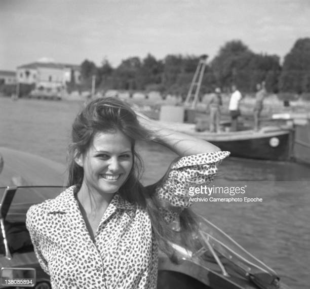 Italian actress Claudia Cardinale standing on a water taxi, the wind messing up with her hair, Lido, venice, 1960.