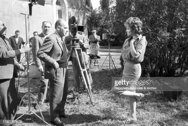 Italian actress Claudia Cardinale taking a break with Italian director Luigi Comencini on the set of La Ragazza di Bube. Italy, 1963