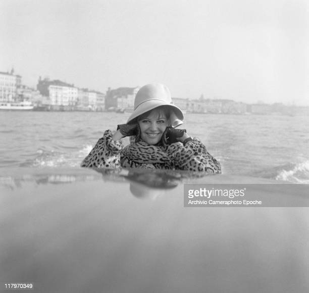 Italian actress Claudia Cardinale, wearing a fun fur and a hat, portrayed on a taxi boat, leaning on the roof top, St Mark's basin, Venezia 1958.