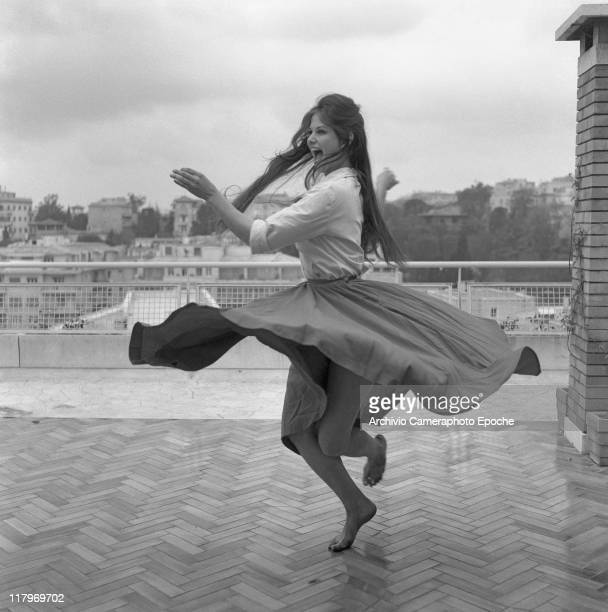 Italian actress Claudia Cardinale wearing a shirt and a wide skirt dancing barefoot on a roof terrace in Rome 1959