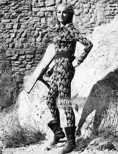 Italian actress Daniela Bianchi holding a gun in a snakeskin catsuit circa 1965