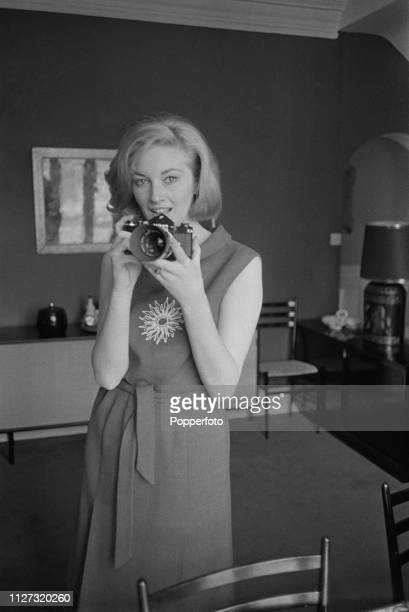Italian actress Daniela Bianchi pictured holding a Nikon SLR camera at home in her apartment in May 1963 Daniela Bianchi currently stars as Tatiana...
