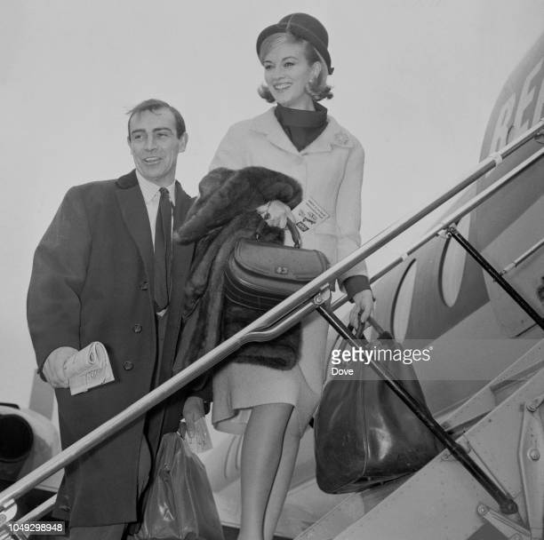 Italian actress Daniela Bianchi pictured with Scottish actor Sean Connery as they climb up steps to a BEA aircraft at London airport on 22nd April...