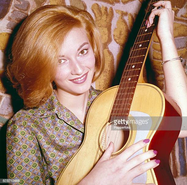 Italian actress Daniela Bianchi who plays Tatiana Romanova in the James Bond film From Russia With Love posed holding an acoustic guitar at home in...