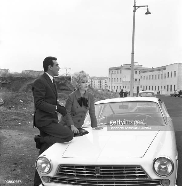 "Italian actress Daniela Rocca and Italian actor Walter Chiari beside a car on the set of the film ""The Attic"". 1962"