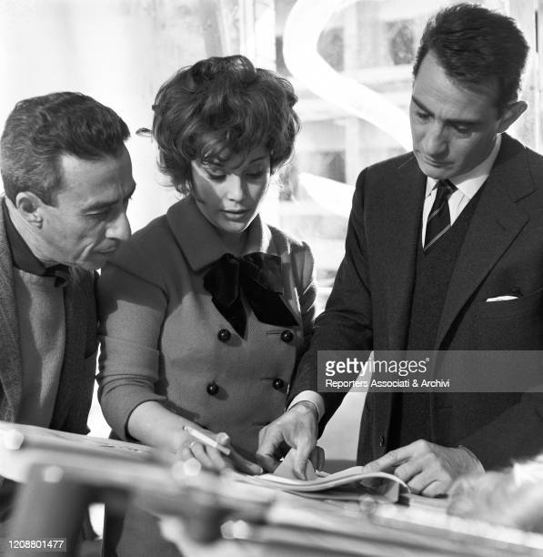 "Italian actress Daniela Rocca, Italian actor Walter Chiari and Italian director Gianni Puccini reading a magazine on the set of the film ""The Attic""...."