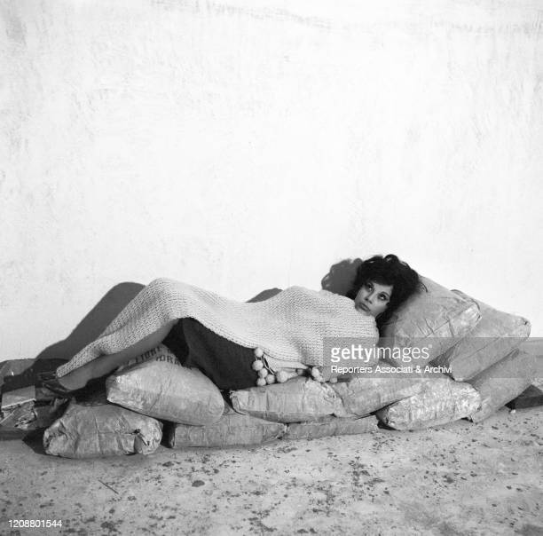 """Italian actress Daniela Rocca lying on some sandbags with a wool blanket on the set of the film """"The Attic"""". 1962"""