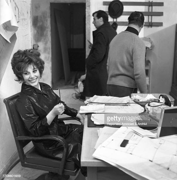 """Italian actress Daniela Rocca sitting at the desk during a break on the set of the film """"The Attic"""". 1962"""