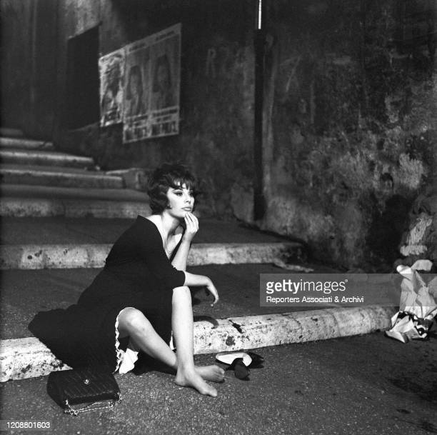 """Italian actress Daniela Rocca sitting barefoot on a staircase on the set of the film """"The Attic"""". 1962"""