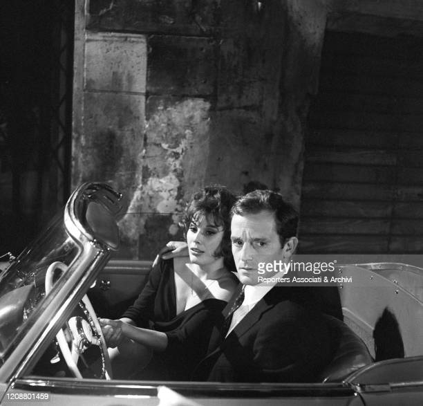"""Italian actress Daniela Rocca sitting in the car beside French actor Philippe Leroy on the set of the film """"The Attic"""". 1962"""