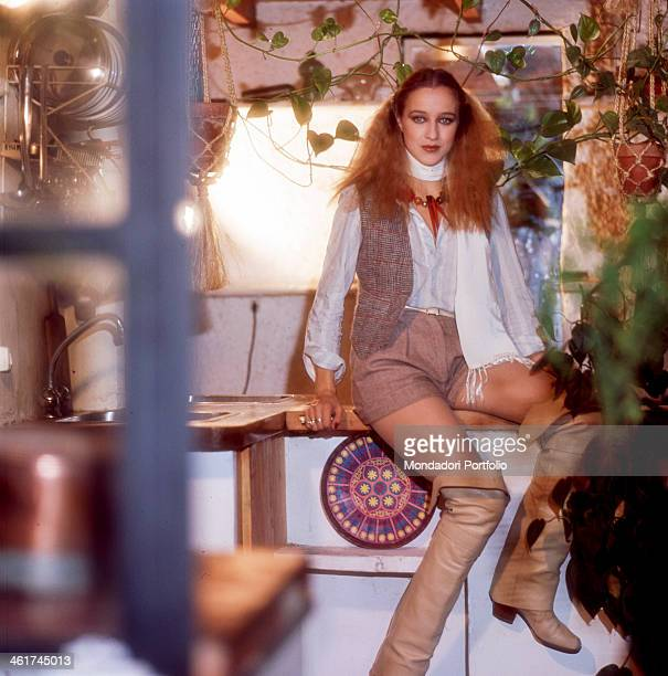 Italian actress Eleonora Giorgi posing sitting on a piece of forniture. 1977
