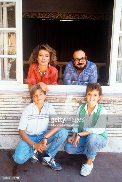 Italian actress Emanuela Giordano and Italian journalist and TV host Maurizio Costanzo leaning out of a window along Italian actors Michael Sebasti...