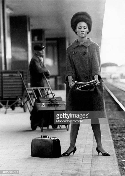 Italian actress Franca Bettoja wearing a coat and a fur hat and reading a newspaper on the platform at the train station. 1960s
