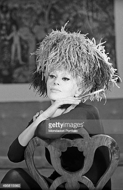 Italian actress Franca Rame posing leaned on the back of chair with a cigarette holder in the hand Milan 1962