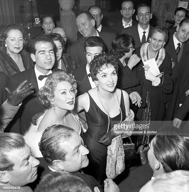 Italian actress Gina Lollobrigida and American actress Martine Carol reaching an awarding ceremony Rome 1956