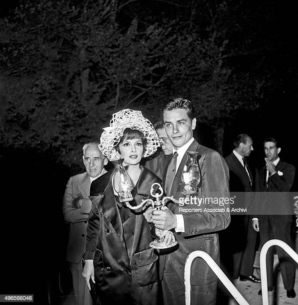 Italian actress Gina Lollobrigida arriving at the party in a villa in Grottaferrata Roma Castles together with French actor Alain Delon holding a...