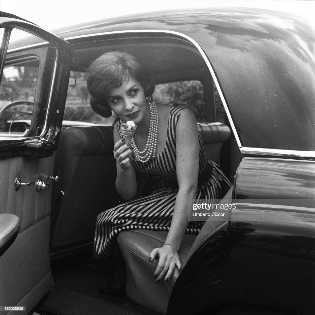 Italian actress Gina Lollobrigida eats an ice-cream in her car, Rome 1955 : News Photo