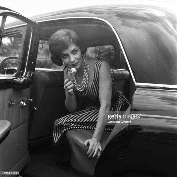 Italian actress Gina Lollobrigida eats an icecream in her car Rome 1955