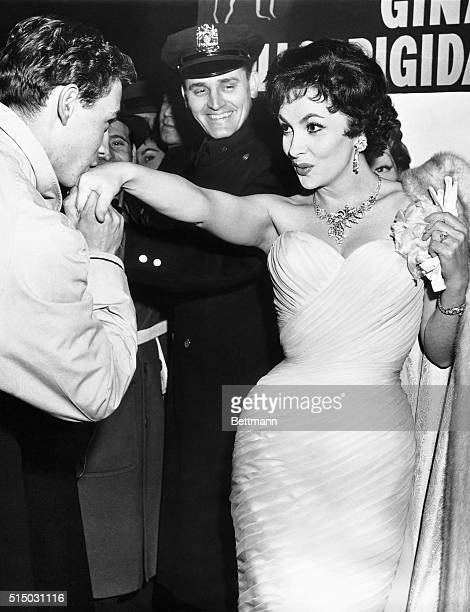 Italian actress Gina Lollobrigida extends her hand for a kiss by admirer Ed Herbich at the New York premiere of her latest film Beautiful But...