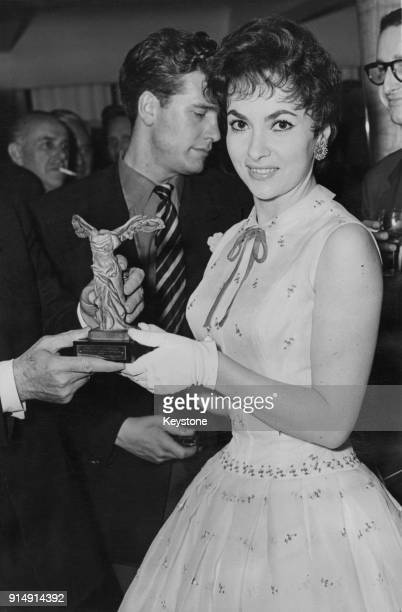 Italian actress Gina Lollobrigida is handed a statuette of the Winged Victory of Samothrace at a reception in her honour at the Savoy Hotel in London...