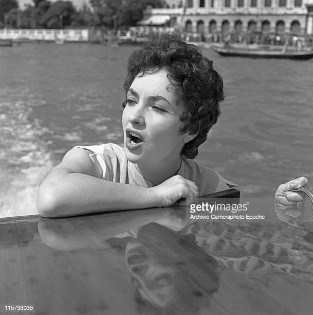 Italian actress Gina Lollobrigida portrayed in a closeup leaning against the water taxi roof singing in the Canal Grande Venice 1954