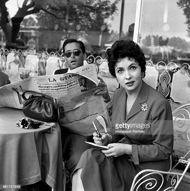 Italian actress Gina Lollobrigida sitting at the table of an outdoor bar with her husband Slovenian doctor Milko Skofic reading the newspaper Rome...