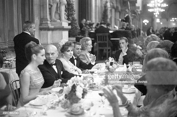 Italian actress Gina Lollobrigida sitting beside Russianborn American actor Yul Brinner talking to his wife DOris Kleiner at a gala dinner for a film...