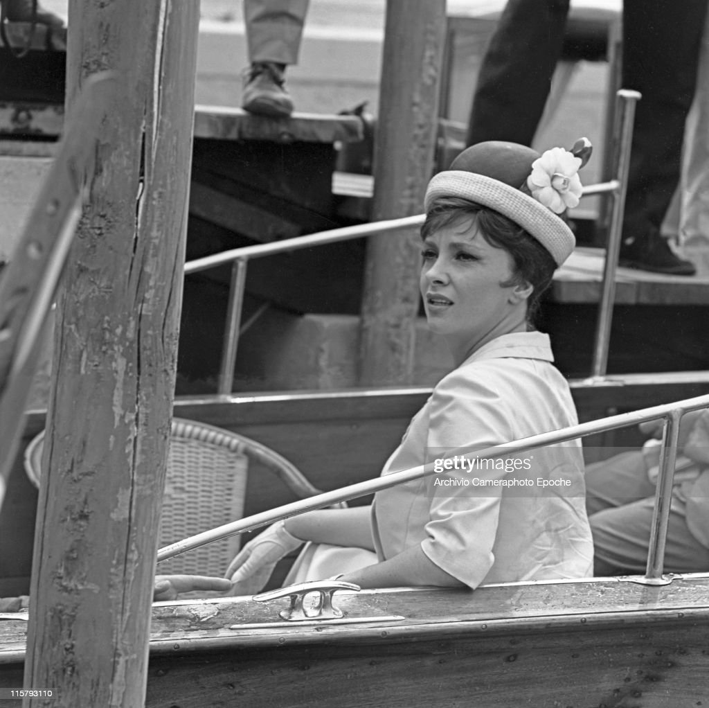 Italian actress Gina Lollobrigida wearing a tailleur, gloves and a bowler hat, sitting in a water taxi, a wharf in the background, Venice, 1962.