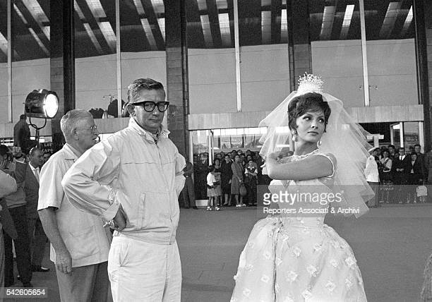 Italian actress Gina Lollobrigida wearing a wedding gown with American director Robert Mulligan at Termini station on the set of Come September Rome...