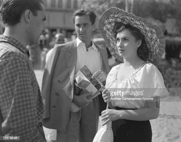 Italian actress Gina Lollobrigida wearing a white shirt a wide brimmed straw hat and holding a handbag talking to Carlo Giovetti her husband Nirko...
