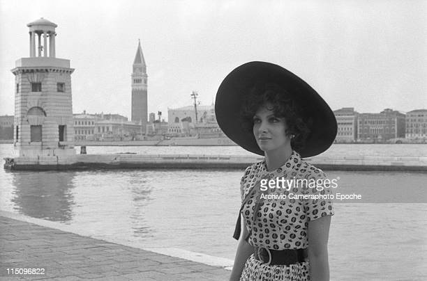 Italian actress Gina Lollobrigida wearing a widebrimmed hat and a fancy dress portrayed from St George Island in Venice with StMark belltower behind...