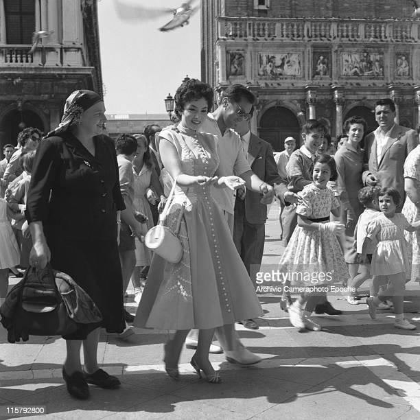 Italian actress Gina Lollobrigida wearing an embroidered dress and holding a handbag walking next to her husband Mirko Scofic in St Mark Square and...